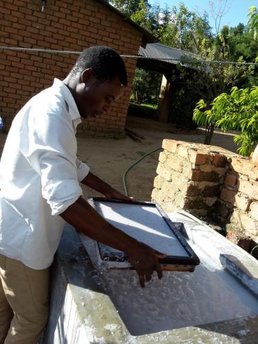 Mit einem zweiteiligen Rahmen, auf dem ein Stofftuch über ein Drahtgitter gespannt ist, schöpft man dann eine möglichst gleichmäßig dicke Schicht aus der Brühe heraus.